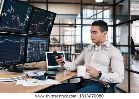 Man trader in formalwear sitting at desk in frot of monitors with charts and data at office holding cup drinking hot coffee browsing social media on smartphone relaxed while trading bot program make Foto stock ©