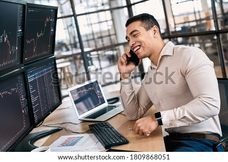 Man trader in formalwear sitting at desk in frot of monitors with charts and data at office talking on smartphone doing online trading training for trainee laughing cheerful having fun explaining Foto stock ©
