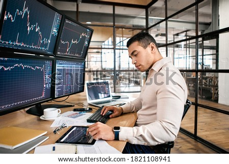 Man trader in formalwear sitting at desk in frot of monitors with charts and data at office using digital tablet monitoring interpreting and analyzing cryptocurrency candle bar pensive stock trading Foto stock ©