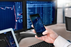 Man trader sitting at desk at office in front of monitors with stocks data holding smartphone browsing application monitoring price changes on candle bar online using digitla devices close-up