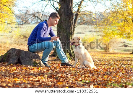 Man training a labrador puppy on an autumn day