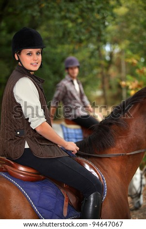 Man training blond teenager to horse ride