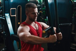 Man training hard at fitness gym. Man doing workout on fitness machine at gym. Gym trainer athlete working out chest muscles doing strength training exercises on gym benchpress equipment.