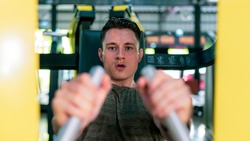Man training hard at fitness gym. Man doing workout on fitness machine at gym. Man working out for chest muscles on gym benchpress equipment. Gym business advertising