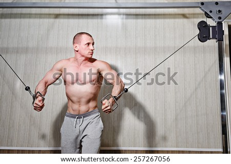 Man trains biceps and triceps in the gym on the simulator