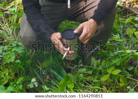 man traveler at a halt with a mug of hot drink and cigarette in the forest