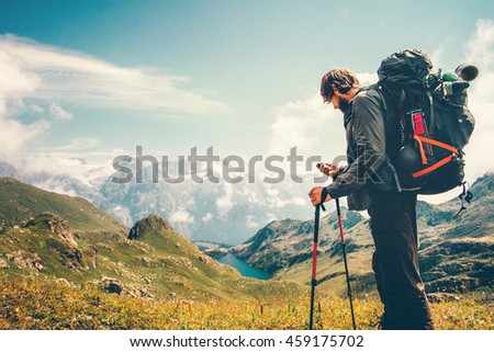 Man Traveler backpacker with gps navigator tracker looking for coordinates Travel Lifestyle concept mountains and lake on background survival adventure vacations outdoor #459175702