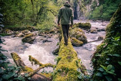 Man Traveler crossing river on log outdoor Lifestyle Travel survival concept