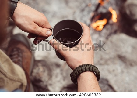 Man traveler hands holding cup of tea near the fire outdoors. Adventure, travel, tourism and camping concept. Hiker drinking tea from mug at camp. Coffee cooked over a campfire on the nature.