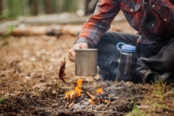 man traveler hands holding mug with water near the fire outdoors. bushcraft, adventure, travel, tourism and camping concept.