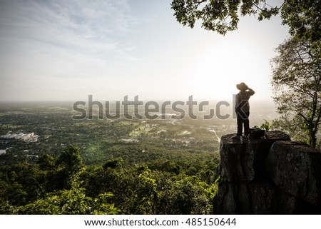 Man traveler is talking on the phone on cliff with beautiful landscape sunset