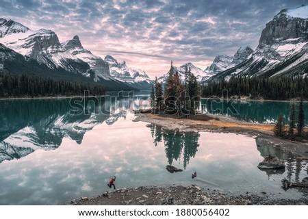 Man traveler jumping on lakeside in Spirit Island on Maligne Lake at Jasper National Park, Canada Stock photo ©