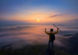 Man Traveler on mountain summit enjoying aerial view hands raised over clouds Travel Lifestyle success concept adventure active vacations outdoor happiness freedom emotions, man hiker top of mountain.