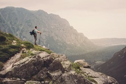 Man Traveler on mountain summit enjoying aerial view. Travel Lifestyle success concept adventure active vacations outdoor happiness freedom emotions. High Tatras mountains.