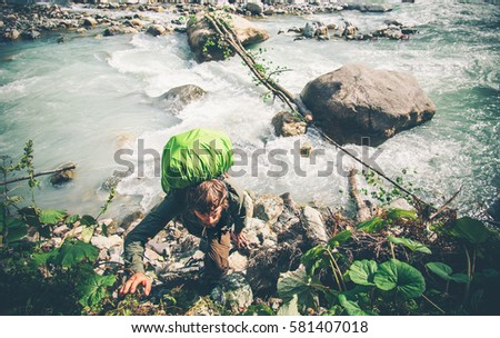 Man Traveler over river climbing Lifestyle Travel extreme survival concept adventure active summer vacations outdoor