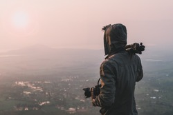 Man traveler photographer and camera taking photo on mountains In the morning the sun rises. Travel Lifestyle hobby concept