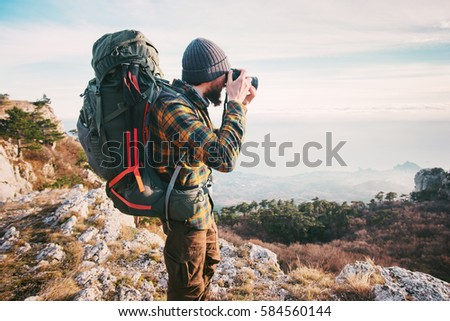 Man traveler photographer with backpack and camera taking photo of mountains Travel Lifestyle hobby concept adventure summer vacations outdoor