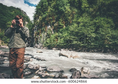 Man traveler photographer with camera taking photo of mountains Travel Lifestyle hobby concept adventure summer vacations outdoor wild nature