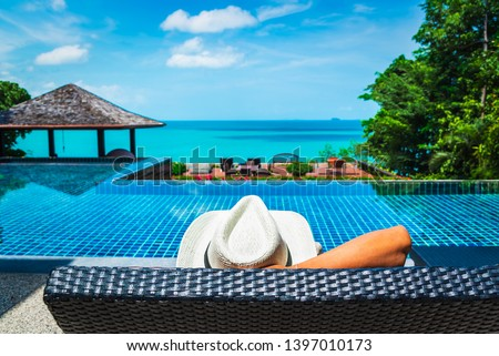 Man traveler relaxing near luxury swimming pool and sea beach, Leisure lifestyle travel Phuket Thailand, Tourist male resting on summer holiday vacation trip, Tourism beautiful destination place Asia