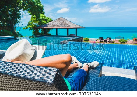 Man traveler relaxing near luxury swimming pool and sea beach, Phuket, Travel in Thailand, Summer vacation concept #707535046