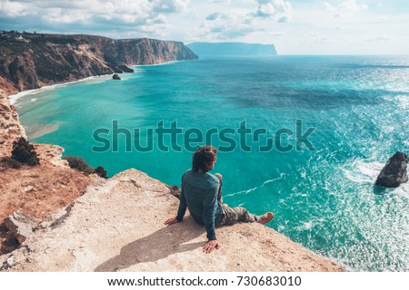 Man traveler sitting on mountain alone and looking at autumn sea landscape. Hiking in cold season. Wanderlust concept scene. #730683010