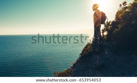 Man traveler stands on the top and enjoys seascape during sunset #653954053