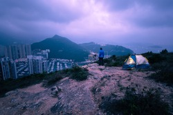 Man traveler Taking photo on top of mountains near of tent camping gear,Male hiking at Yuk Kwai Shan (Mount Johnson) located in Ap Lei Chau,Hong Kong, People living healthy active lifestyle outdoors