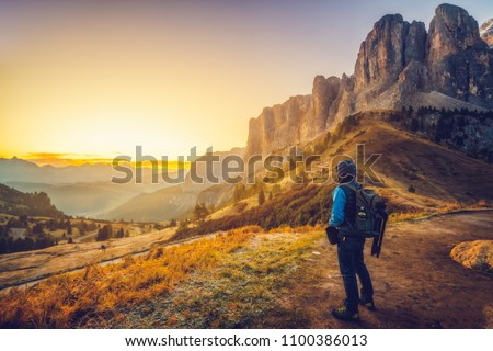 Man traveler traveling alone in breathtaking landscape of Dolomites Mounatains at sunrise in summer in Italy. Travel Lifestyle wanderlust adventure concept. Wanderer in wilderness. #1100386013
