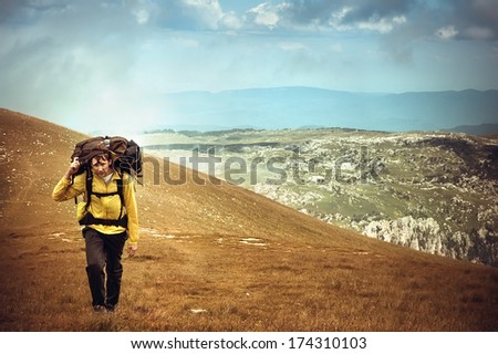 Man Traveler with Backpack hiking in Mountains Survival into the wild