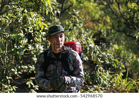 Man Traveler with backpack trekking in forest, Hikers trekking  with backpacks in forest #542968570