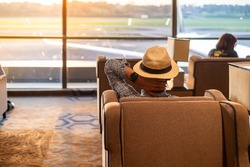 man traveler with hat looking to airplane in the morning sunrise, Asian passenger sitting and relax in modern lounge at international airport terminal. Travel concept