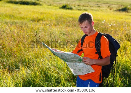 Man traveler with map in hand looking at it against the background of sunlit meadows