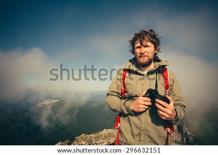 Man Traveler with photo camera and backpack hiking outdoor Travel Lifestyle survival concept with mountains clouds on background