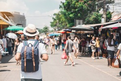 Man traveling backpacker with hat, Asian traveler standing at Chatuchak Weekend Market, landmark and popular for tourist attractions in Bangkok, Thailand. Travel concept