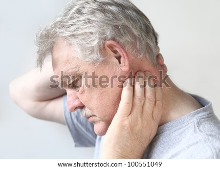 man tries to move his stiff, painful neck