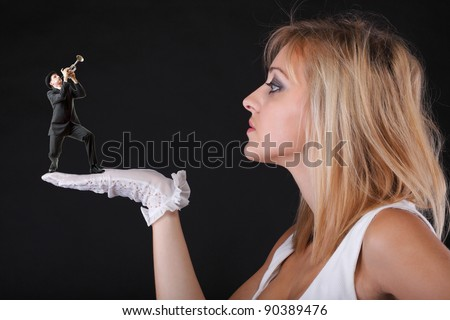 Man trumpet play for beautiful blonde woman in white gloves black background