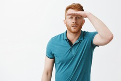 Man trying find joke, looking far away, squinting and holding palm on forehead to cover eyes from sunlight and see clearly, standing focused and interested in greet polo shirt over grey wall