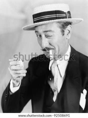 Man trying to light a broken cigarette winking at the camera