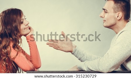 Man trying to reconcile with woman. Couple making up after quarrel. Husband reaching out to wife. Instagram filtered.