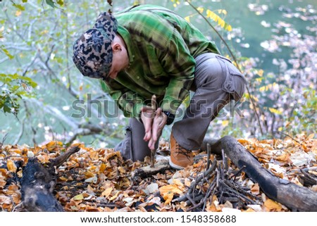 Man trying to start a fire in the wild using primitive method of friction. Practical survival skills - Image #1548358688