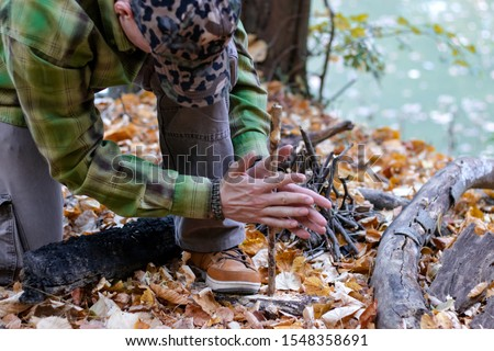 Man trying to start a fire in the wild using primitive method of friction. Practical survival skills - Image #1548358691