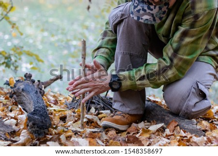 Man trying to start a fire in the wild using primitive method of friction. Practical survival skills - Image #1548358697