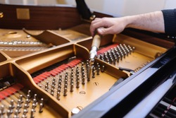 Man tuning traditional upright piano for jazz. hand of a man tuning piano, close up