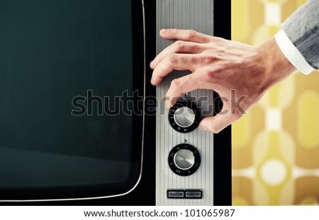 Man  turning channel knob on retro television