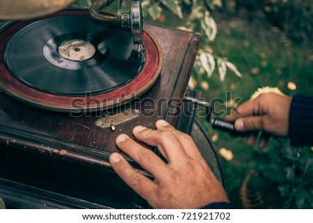 Man twists a pen on a vintage gramophone to play music, selective focus, retro toned Zdjęcia stock ©