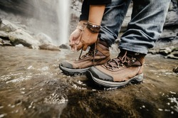 Man tying hiking boot's shoelaces, waterfall background.