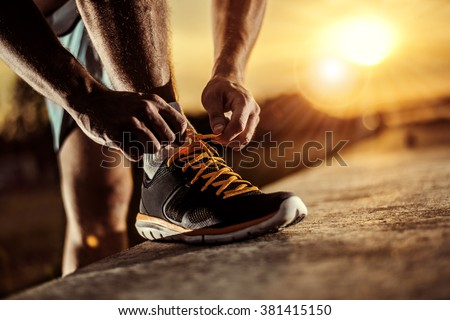 Shutterstock Man tying jogging shoes