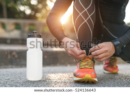 Man tying jogging shoes.A person running outdoors on a sunny day.Focus on a side view of two human hands reaching down to a athletic shoe. #524136643