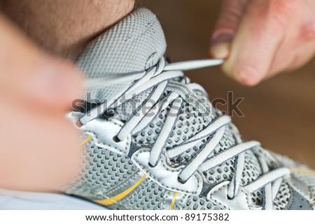 Man tying sports shoe at gym before workout