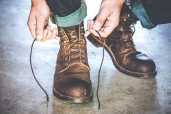 Man tying the laces on leather shoes boot.